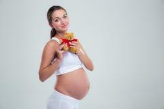 Pregnant woman holding teddy bear Stock Photos