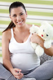 Pregnant woman holding teddy bear. Young pregnant woman holding teddy bear Royalty Free Stock Images