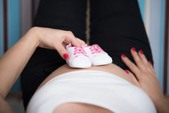 Pregnant woman holding a tiny baby shoes on her belly Stock Images