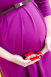 Pregnant woman holding toy car. Pregnant in a purple dress holding a red toy car next to the tummy Stock Photo