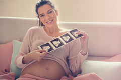 Pregnant woman holding ultrasound of her baby. royalty free stock photography