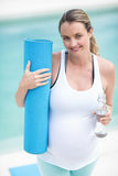 Pregnant woman holding water bottle and mat Stock Photo