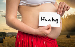 Pregnant woman holding white with inscription: It`s a boy Stock Photography