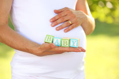 Pregnant woman holding word baby Royalty Free Stock Photography