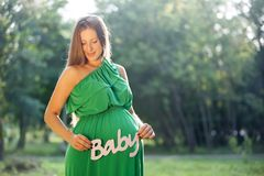 Pregnant woman holding  word BABY Royalty Free Stock Images