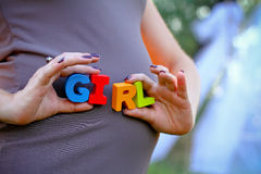 Pregnant woman holding the word girl Stock Images