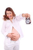 Pregnant woman holds at arm alarm clock Stock Photo