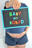 Pregnant woman holds a baby on board colored text on blackboard Royalty Free Stock Image
