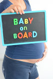 Pregnant woman holds a baby on board colored text on blackboard over her belly Stock Photos