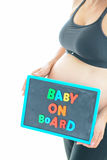 Pregnant woman holds a baby on board colored text on blackboard over her belly Royalty Free Stock Photo