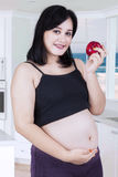 Pregnant woman holds red apple Royalty Free Stock Photography
