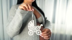 Pregnant woman holds the symbol of maternity - toy baby pram on a string. Unrecognizable girl with big belly at home stock video