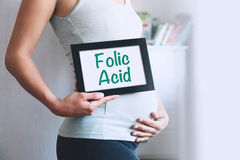 Pregnant woman holds whiteboard with text message - FOLIC ACID. Pregnancy, parenthood, preparation and expectation concept. Close-up, copy space, indoors Royalty Free Stock Photography