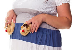 Pregnant woman holing baby's bootees at her belly Stock Photography