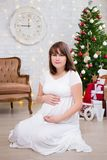 Pregnant woman at home with decorated christmas tree, vintage so. Attractive pregnant woman at home with decorated christmas tree, vintage sofa, lights and gifts stock photo