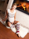 Pregnant woman at home near the fireplace Royalty Free Stock Image