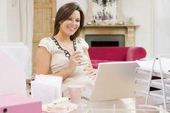 Pregnant woman in home office with laptop eating Royalty Free Stock Photos