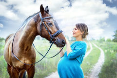 Pregnant woman with horse Royalty Free Stock Image