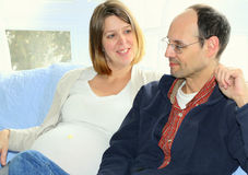 Pregnant woman with husband. A pregnant woman is sitting with her arm around her husband Stock Image