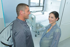 Pregnant woman with husband arriving at hospital Stock Images