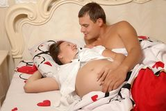 Pregnant woman with the husband on a bed Stock Images