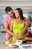 Pregnant Woman And Husband Having Breakfast In Kitchen Stock Image