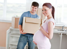 Pregnant woman and husband holding box in kitchen Stock Photo