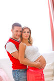 Pregnant woman with husband hugging her tummy Stock Image