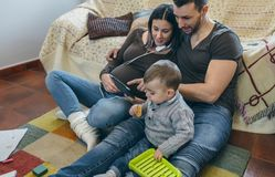 Pregnant woman and husband looking tablet while son plays. Pregnant women and her husband looking at the tablet while their little son plays Royalty Free Stock Photo