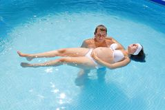 Pregnant woman with husband in pool Stock Photography