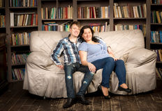 Pregnant woman and husband posing on couch at living room Royalty Free Stock Image