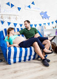 Pregnant woman and husband relaxing on couch at living room Stock Photo