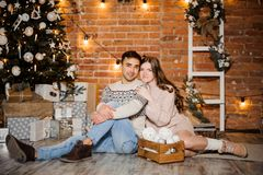Pregnant woman with husband sitting near the Christmas tree and gift boxes. Happy pregnant women with husband in sweaters sitting near the Christmas tree and Royalty Free Stock Images