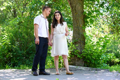 Pregnant woman with husband walking in the city park, family portrait, summer season, green grass and trees Stock Photography