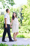 Pregnant woman with husband walking in the city park, family portrait, summer season, green grass and trees Stock Photos