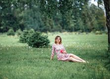 Pregnant woman inpink dress sitting on grass and touching bump whilst holding pink rose girl waiting royalty free stock photos