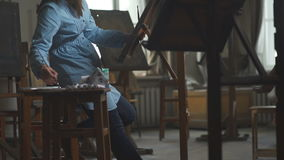 A pregnant woman is inspired to paint a picture. A woman painter. Young woman painter in blue dress draws behind an easel in a light and spacious art studio. A Stock Image