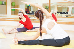 Pregnant woman with instructor doing fitness ball exercise Royalty Free Stock Photos