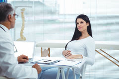 Pregnant woman interacting with doctor at clinic Stock Photography