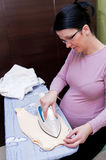 Pregnant woman ironing Stock Image