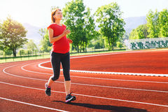 Pregnant woman jogging on running track in stadium. stock photo