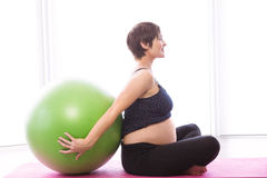 Pregnant woman keeping in shape Stock Image
