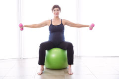 Pregnant woman keeping in shape Stock Images