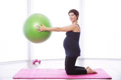 Pregnant woman keeping in shape Stock Photo