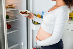 Pregnant woman keeping strawberries in fridge Royalty Free Stock Photography