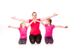 Pregnant woman with kids exercising isolated Royalty Free Stock Photos