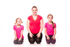 Pregnant woman with kids exercising isolated Royalty Free Stock Images