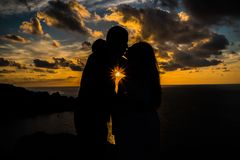 Pregnant woman kissing her partner at sunset before birth for a photosession stock photo