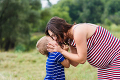 Pregnant woman kissing her son Royalty Free Stock Image