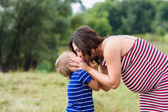 Pregnant woman kissing her son Stock Image